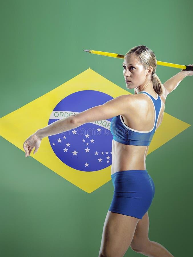 Vue de côté de javelot de lancement d'athlète féminin contre le drapeau brésilien photo libre de droits
