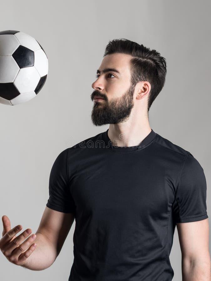 Vue de côté de jeune boule de lancement barbue du football ou de footballeur photographie stock