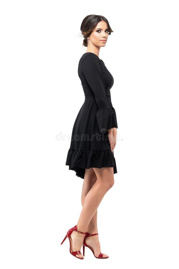 Vue de côté de jeune femme dans la robe noire regardant l'appareil-photo avec le vent dans des cheveux de petit pain photos libres de droits