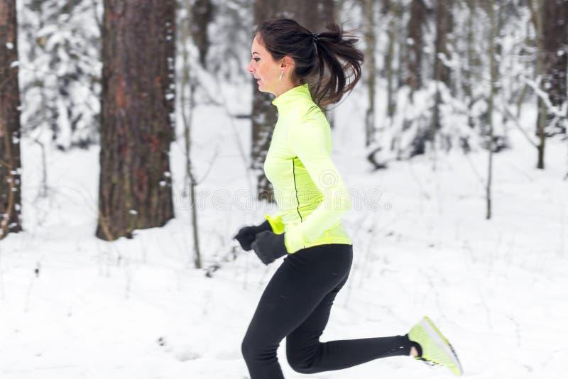 Vue de côté de jeune femme sportive fonctionnant dans la séance d'entraînement de formation de rue d'hiver de matin images stock