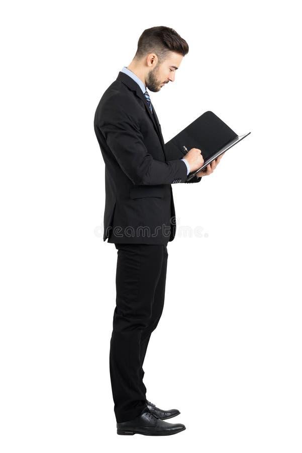 Vue de côté de jeune homme d'affaires dans le contrat de signature de costume images stock