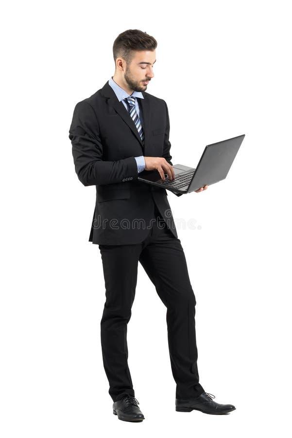 Vue de côté de jeune homme d'affaires dans le costume utilisant l'ordinateur portable photographie stock