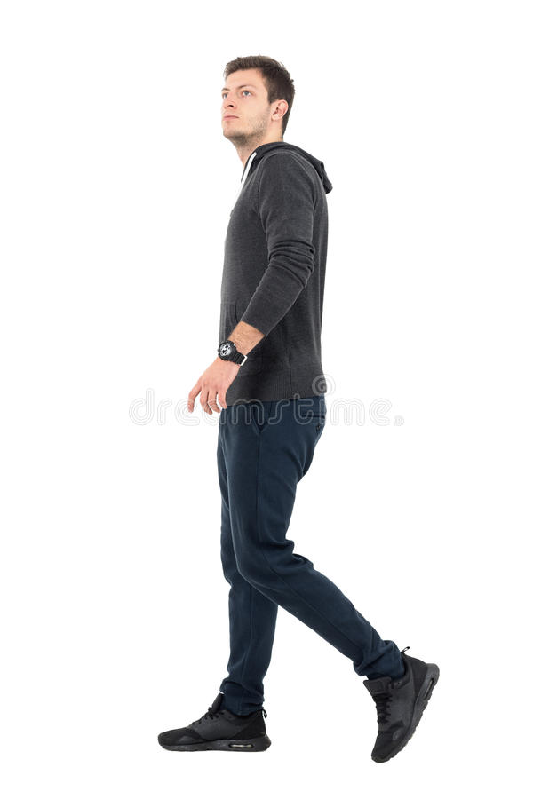 Vue de côté de jeune homme sportif bel dans la recherche de marche de pull molletonné et de survêtement de sport photographie stock libre de droits
