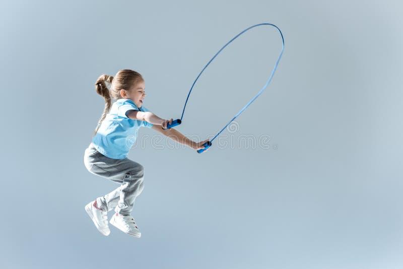 Vue de côté de l'exercice humping de fille heureuse avec la corde à sauter images stock