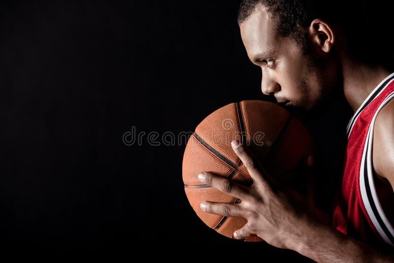 Vue de côté de l'homme sportif africain tenant la boule de basket-ball image libre de droits