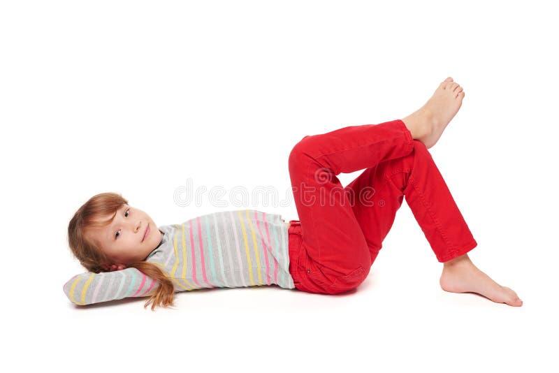 Vue de côté de la fille de sourire d'enfant se trouvant sur le plancher photos stock