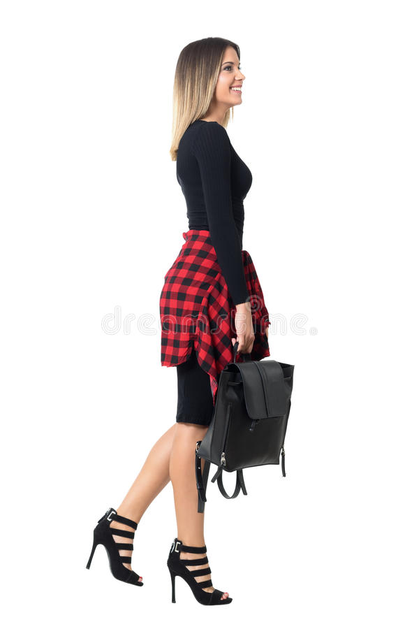 Vue de côté de la jeune jolie fille d'étudiant de style occasionnel marchant avec le sac noir recherchant photo libre de droits