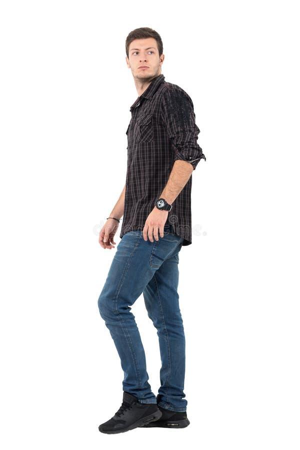 Vue de côté de regarder de marche de jeune homme occasionnel au-dessus de l'épaule photographie stock libre de droits