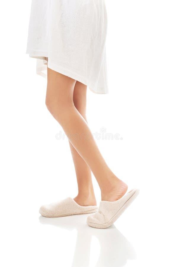Vue de côté des pieds femelles dans des pantoufles blanches photographie stock
