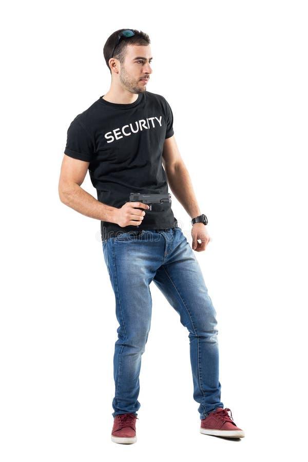 Vue de côté du jeune flic alerté tenant l'arme à feu regardant loin photographie stock libre de droits