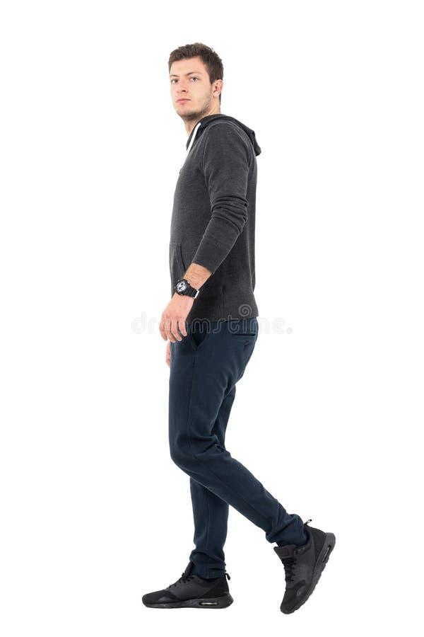 Vue de côté du jeune homme dans les vêtements de sport marchant et regardant l'appareil-photo image stock