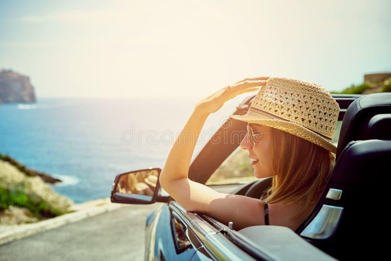 Vue de côté sur la femme de sourire dans la voiture convertible photos stock