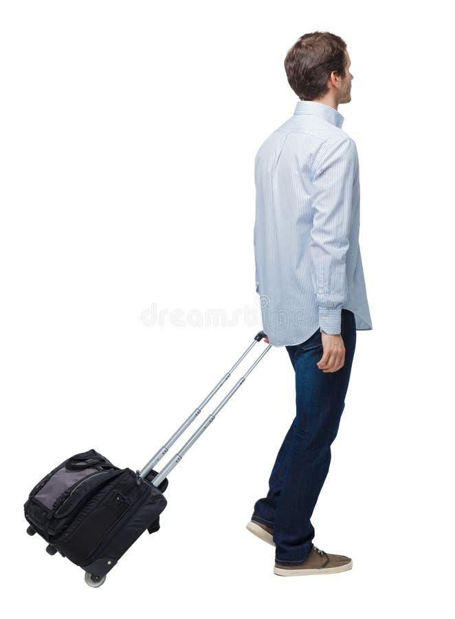 Vue de c?t? de l'homme de marche d'affaires avec la valise parlant au t?l?phone image stock