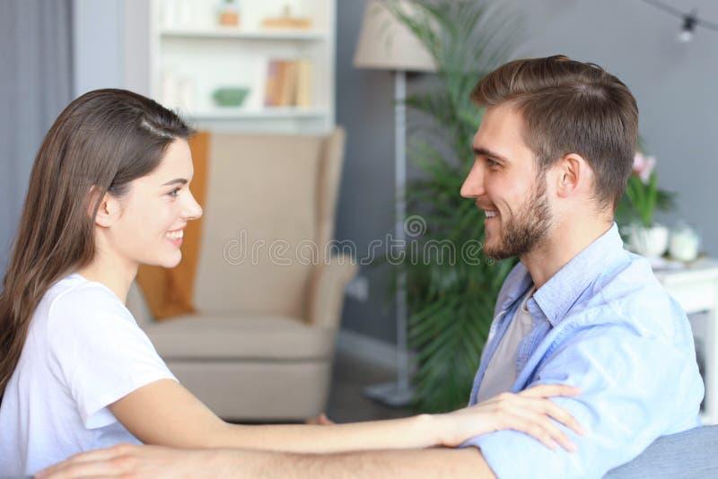 Vue de c?t? de se reposer parlant de couples sur un divan et de se regarder ? la maison images libres de droits