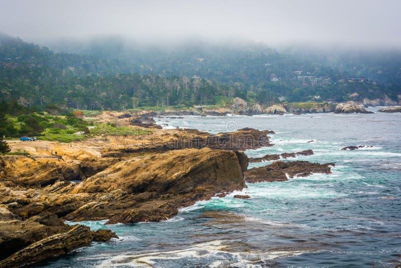 Vue de côte et de brouillard rocheux au-dessus des collines éloignées au St de Lobos de point photo libre de droits
