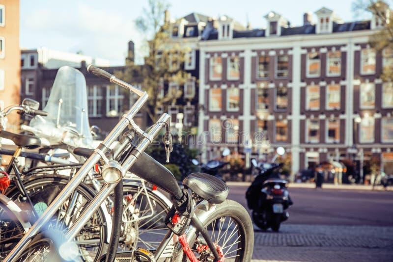 Vue de carte postale : faites du vélo le stationnement sur la rue européenne de ville, Amsterdam photographie stock