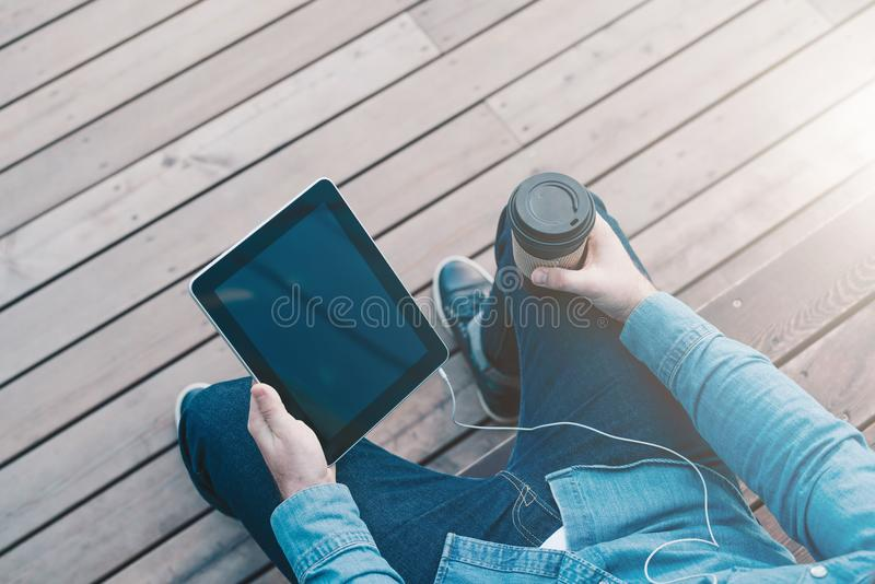 Vue de ci-avant Le plan rapproché du comprimé numérique avec l'écran vide noir et la tasse de café dans des mains de hippie équip photographie stock