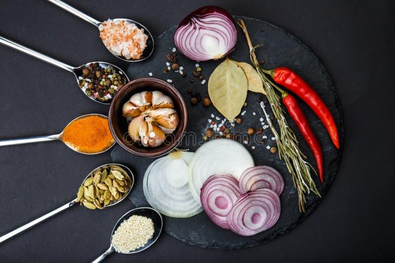 Vue de ci-avant Sur un panneau rond, des légumes pointus et une cuillerée d'épices images stock