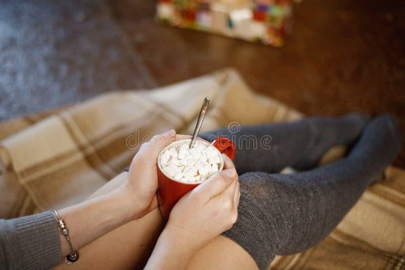 Vue de ci-dessus comme fille dans le chandail chaud dans des ses mains tenant la tasse de cacao avec des guimauves sur le fond du image libre de droits