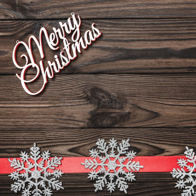 Vue de ci-dessus d'une inscription de Joyeux Noël sur la place de brun foncé, fond en bois avec le ruban rouge image stock