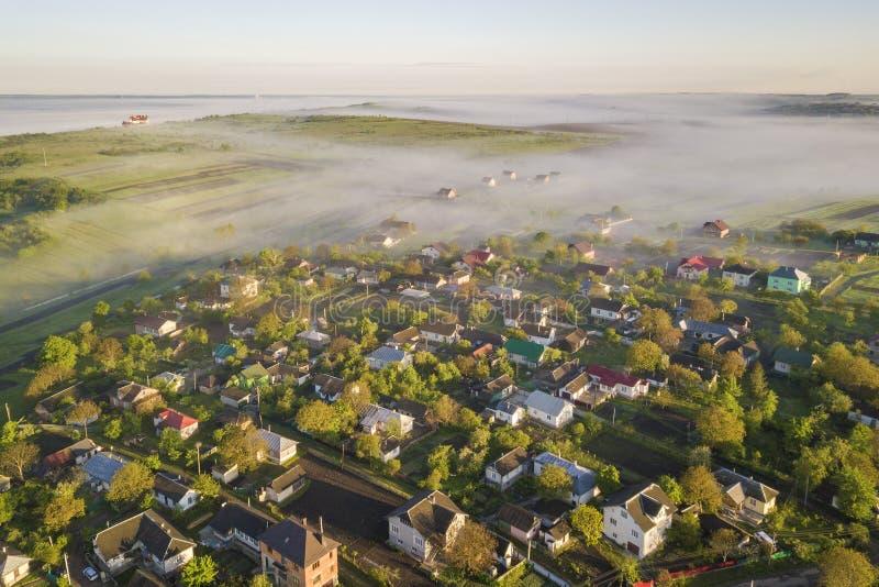 Vue de ci-dessus du brouillard blanc sur des toits de maison de village parmi les arbres verts sous le ciel bleu lumineux Panoram image stock