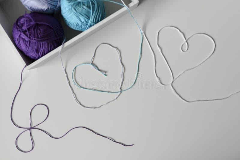 Vue de ci-dessus sur des coeurs des brins colorés de laine sortant du boîtier blanc avec des boules de fil à tricoter photo libre de droits
