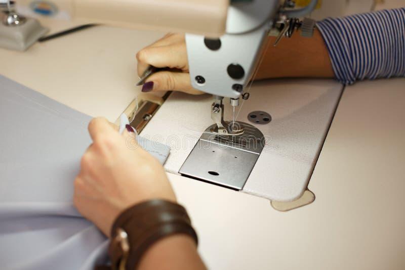 Vue de ci-dessus sur des mains de tailleur féminin travaillant à la machine à coudre industrie de robe photos stock