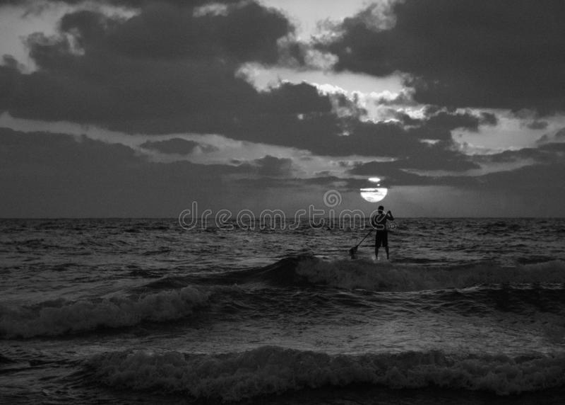 Vue de coucher du soleil d'été d'une plage sous un ciel nuageux avec une silhouette simple de surfer de petite gorgée en noir et  photos libres de droits