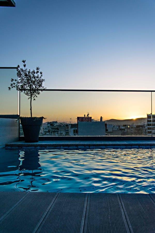 Vue de coucher du soleil par la piscine sur la zone urbaine photos stock
