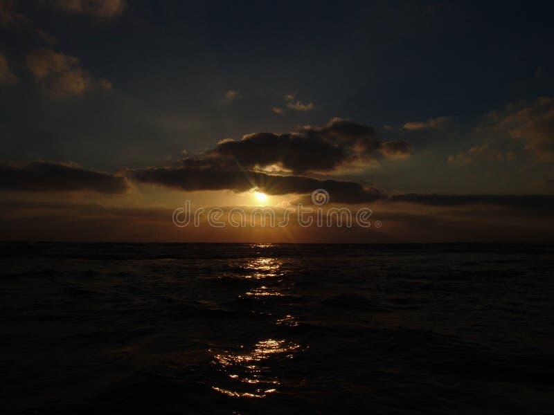 Vue de coucher du soleil sur une plage sablonneuse calme avec le ciel nuageux et la lumière d'or photo stock