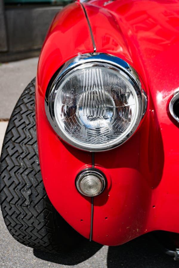 Vue de détail de l'amortisseur et du phare avant d'une voiture de sport rouge classique d'Austin Healey images stock