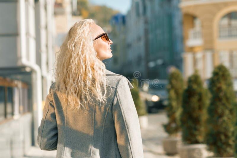 Vue de derrière de la jeune femme blonde marchant le long de la rue de ville, jour ensoleillé d'automne images libres de droits