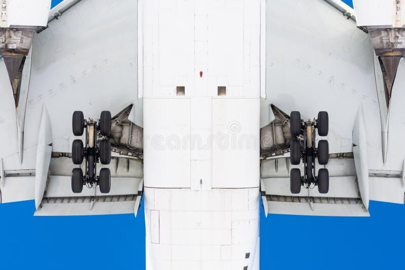 Vue de dessous sous l'avion de vol avant le débarquement, en détail le châssis, les ailes, les ailerons, le fuselage et le moteur images stock