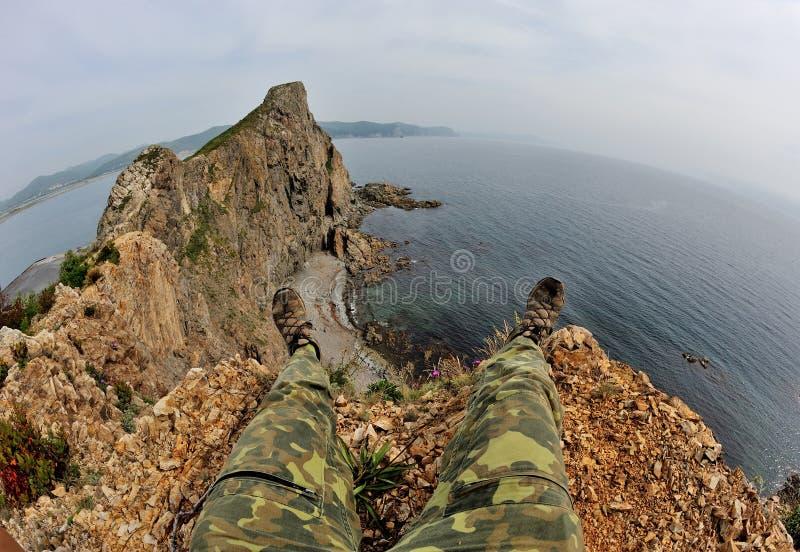 Vue de deux jambes au-dessus de falaise et de baie de danger image libre de droits