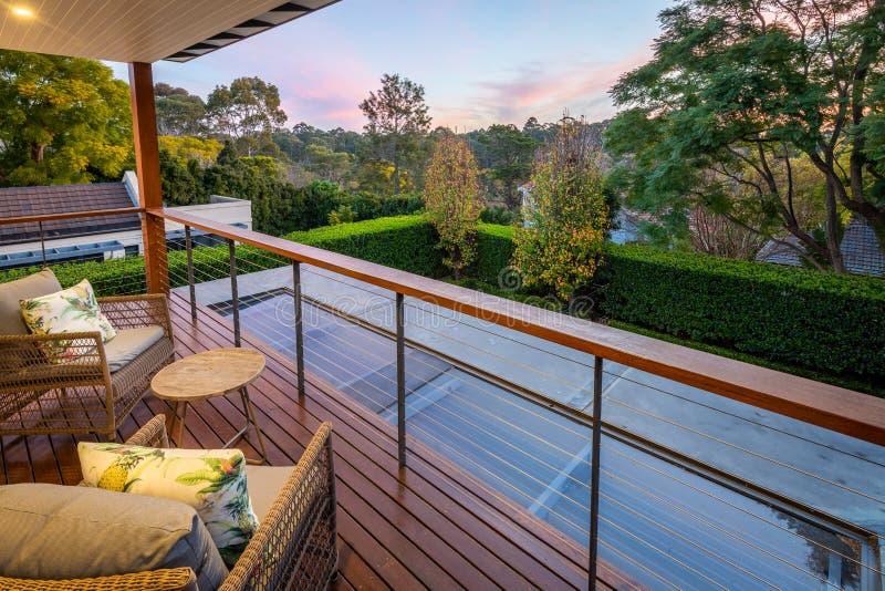 Vue de district depuis le balcon terrasse d'une maison de banlieue au-dessus d'un jardin paysager au crépuscule / au coucher du s image stock