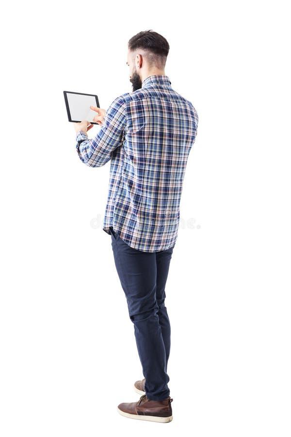 Vue de dos de l'homme barbu d'affaires poussant le bouton sur l'écran tactile de blanc de tablette image libre de droits