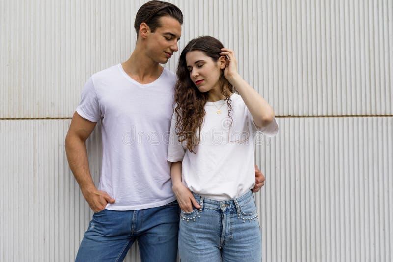 Vue de face de beaux jeunes couples étreignant, regardant la caméra et souriant tout en se tenant dehors images stock