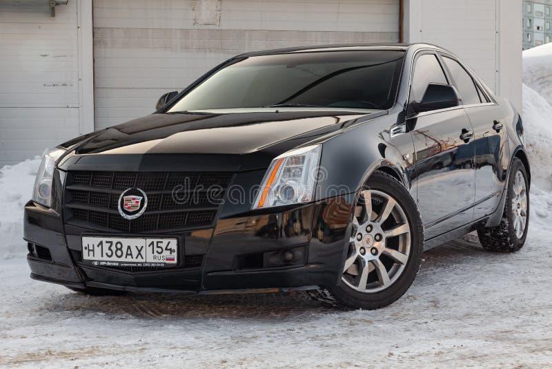 Vue de face de Cadillac CTS dans la couleur noire après nettoyage avant vente à un jour d'hiver et à un arrière-plan de neige images stock