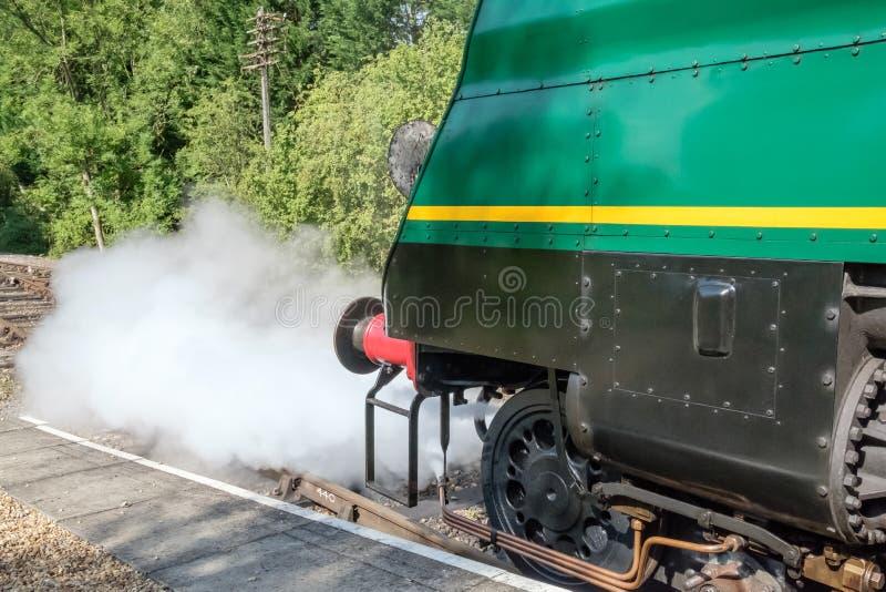 Vue de face détaillée d'une locomotive à vapeur célèbre et britannique montrant laisser outre de la vapeur tandis qu'à une gare f image libre de droits