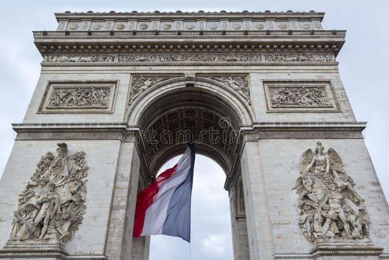 Vue de face d'Arc de Triomp avec le drapeau de la France ondulant en vent sur l'endroit de Gaulle à Paris, France images stock