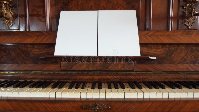 Vue de face d'un piano antique avec le clavier ouvert et deux feuilles de papier blanc sur le soutien des notes musicales photographie stock
