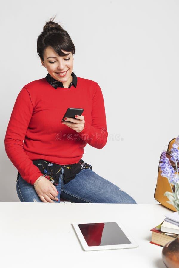 Vue de face d'une belle femme latine s'asseyant sur un tabouret tout en à l'aide d'un téléphone portable au bureau sur le fond bl images stock