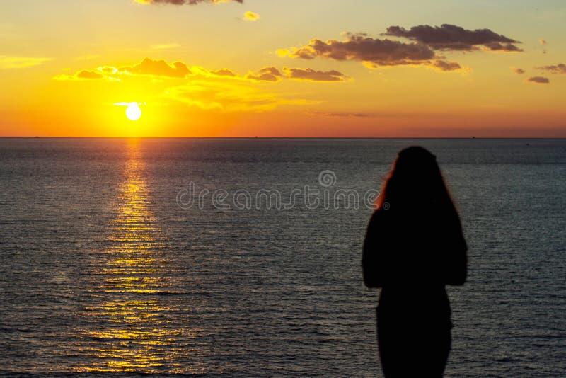 Vue de face d'une lumière arrière de la silhouette fidèle de femme tenant le soleil sur la plage au lever de soleil avec un fond  photos stock