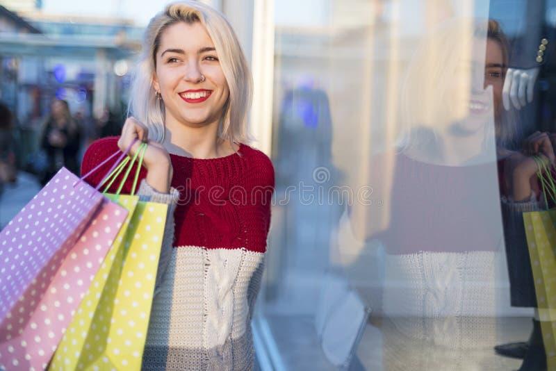 Vue de face d'une position de sourire de jeune femme à un centre commercial tout en regardant à la caméra images libres de droits
