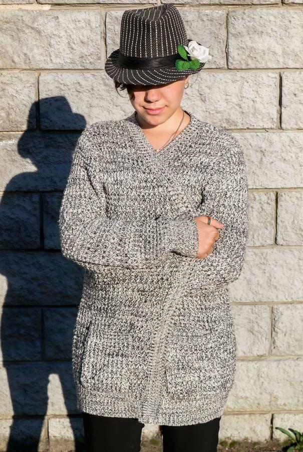 Vue de face de fille de l'adolescence regardant vers le bas dans l'habillement et l'ombre gris image libre de droits