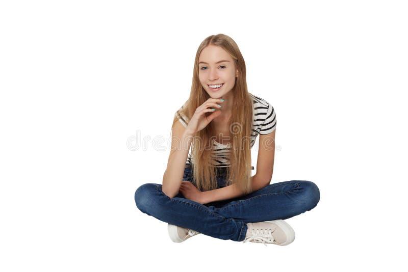 Vue de face de la belle femme de sourire s'asseyant sur le plancher photos libres de droits