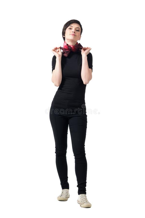 Vue de face de la jeune brune mince féminine attachant et ajustant le foulard images libres de droits