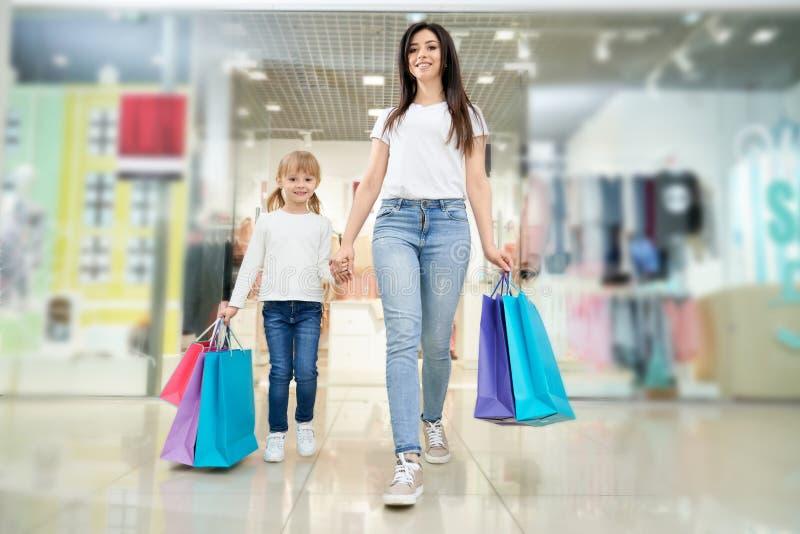 Vue de face des achats de femme ainsi que la fille dans le mail photographie stock