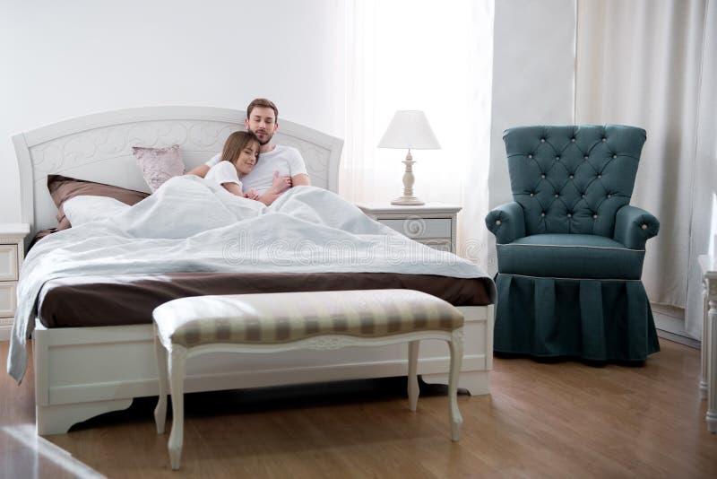 Vue de face des couples étreignant dans la chambre à coucher photos libres de droits