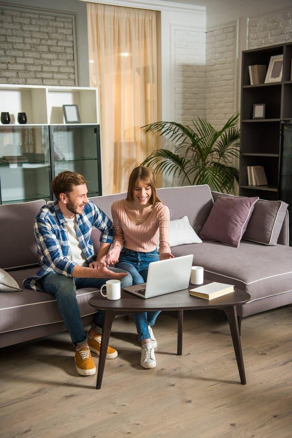 Vue de face des couples de sourire sur le divan utilisant l'ordinateur portable dans confortable photo libre de droits